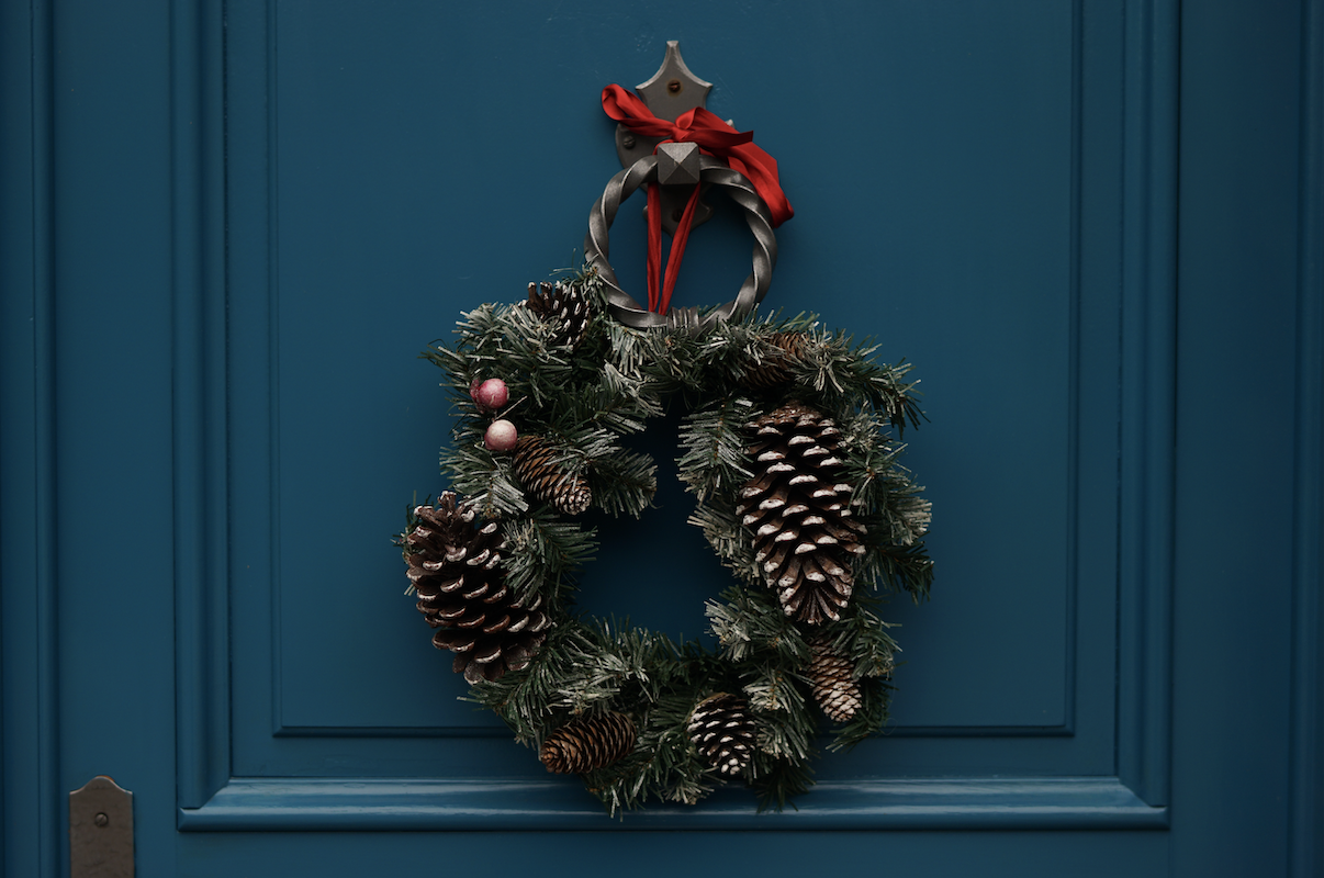 wreath filled with oversized pine cones tied with red ribbon onto a crisp cobalt blue door